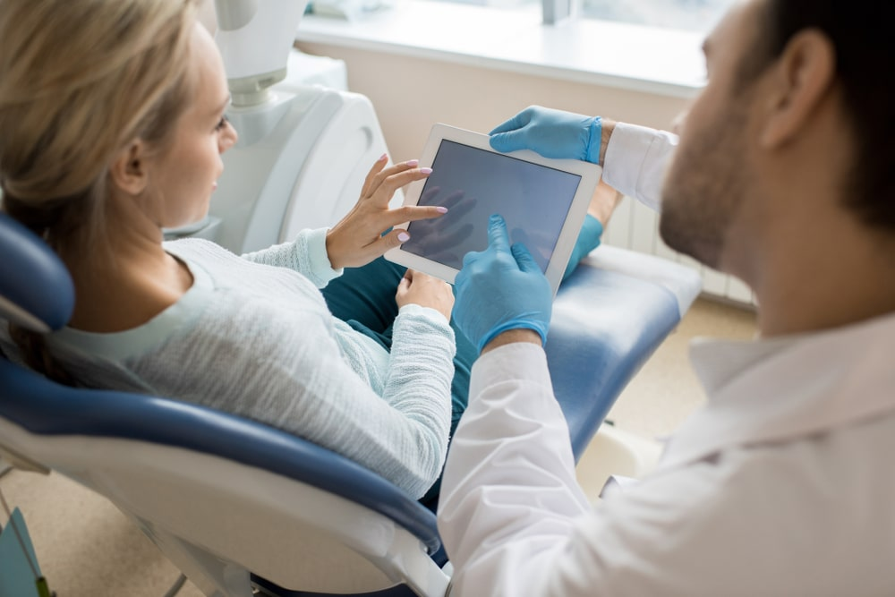 Dentist having a discussion with female patient and both are looking at a tablet