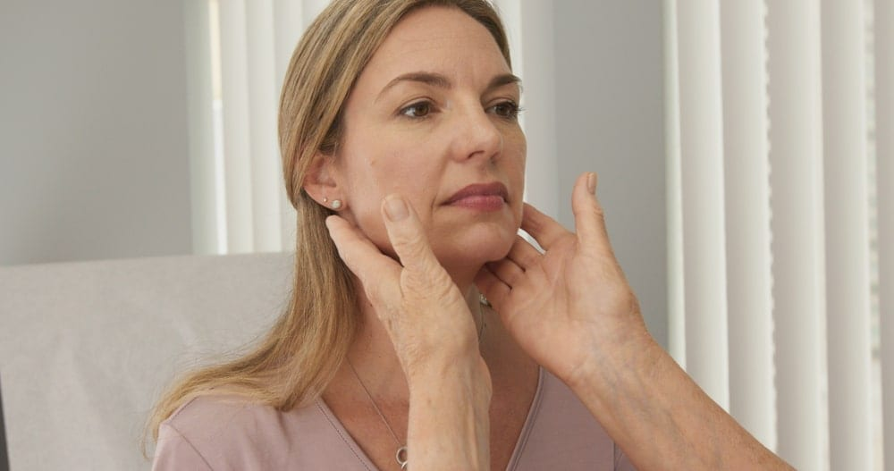 Doctor's hands checking a woman's lymph nodes