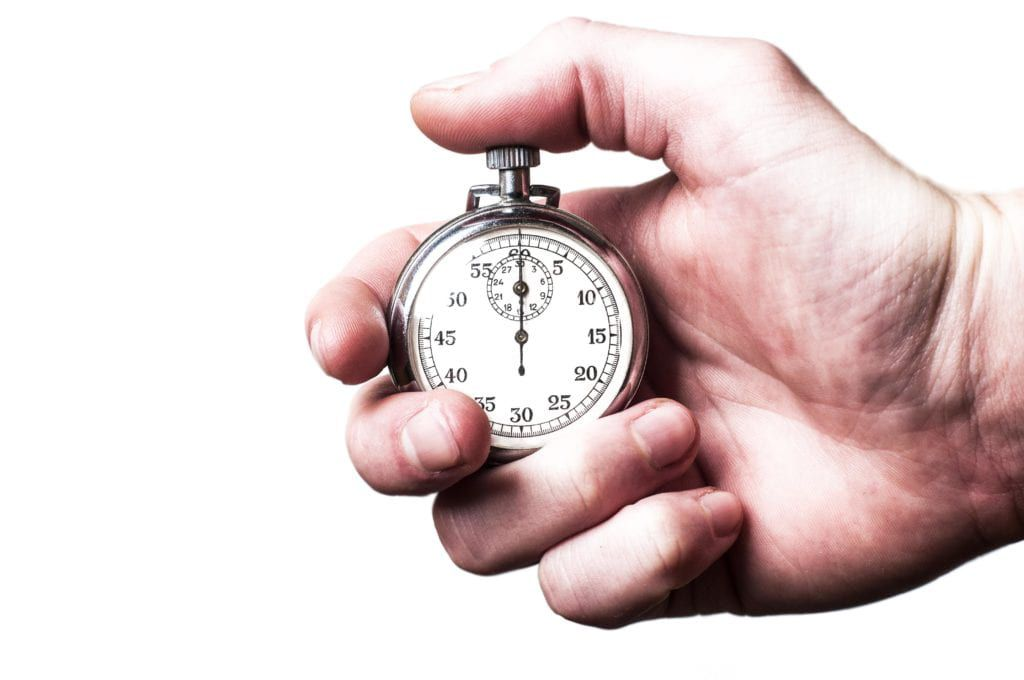 Male hand holding a stopwatch on a white background
