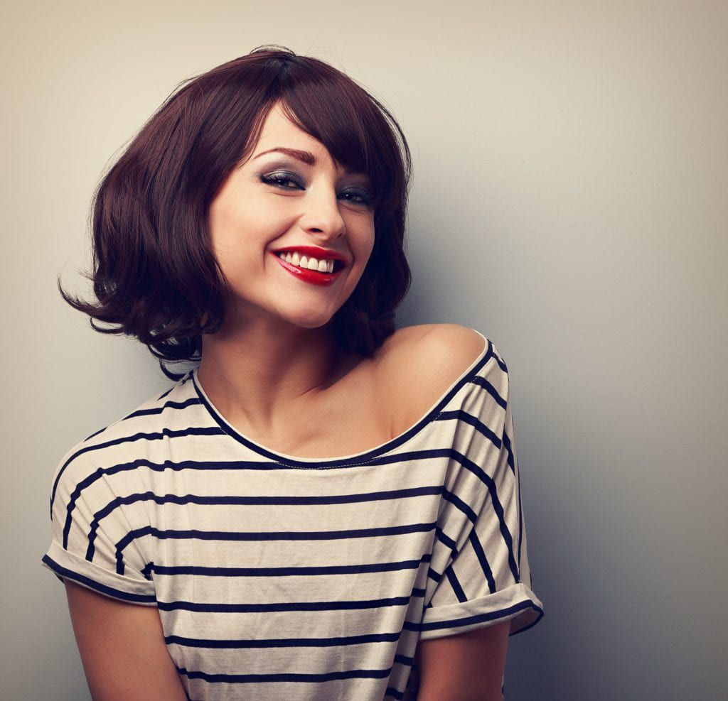 Woman in striped shirt smiling with red lipstick